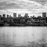 Newport Beach skyine sunrise black and white photo with Balboa Island homes, Newport Harbor, and Fashion Island office buildings. Newport Beach is an affluent coastal city in Orange County Southern California. Photo is high resolution. Copyright ⓒ 2017 Paul Velgos with All Rights Reserved.