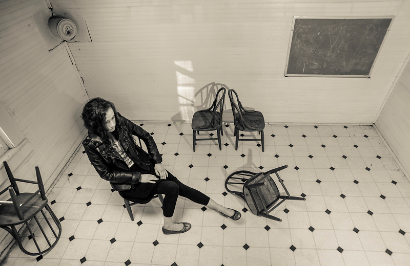 A 16-year-old teenage girl wearing a black leather jacket and black pants sits in a child's wooden chair in a 19th Century church in Pittsboro, NC.