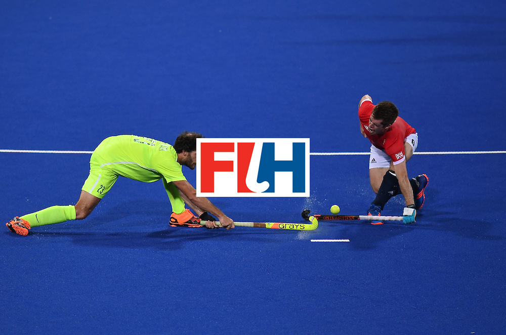 Brazil's Chris McPherson (L) and Britain's Henry Weir fight for the ball during the men's field hockey Brazil vs Britain match of the Rio 2016 Olympics Games at the Olympic Hockey Centre in Rio de Janeiro on August, 9 2016. / AFP / MANAN VATSYAYANA        (Photo credit should read MANAN VATSYAYANA/AFP/Getty Images)