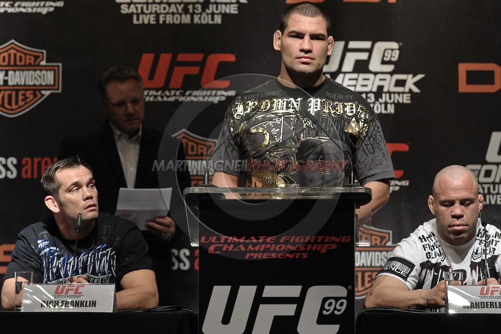 """COLOGNE, GERMANY, JUNE 11, 2009: Cain Velasquez (center) addresses the media, flanked by Rich Franklin (left) and Wanderlei Silva (right) at the pre-fight press conference for """"UFC 99: The Comeback"""" inside the Hyatt Regency Hotel in Cologne, Germany on June 11, 2009."""