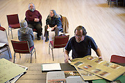 Craig Wortman searches for a visual aid while teaching a class on dairy farming with his wife Joan, left, at the Bethel (Vt.) Town Hall Tuesday, March 15, 2016. After seeing negative reports about dairy farms and their treatment of animals in the media, the Wortmans decided to share their farm experiences and practices with the public through the annual pop-up university. Only two students, Cynthia and Giovanni Quilici, of Randolph, Vt. attended. (Valley News - James M. Patterson) Copyright Valley News. May not be reprinted or used online without permission. Send requests to permission@vnews.com.
