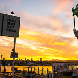 Newport Beach California Balboa Fun Zone high resolution sunrise panoramic photo. Includes the Balboa Island Auto Ferry sign, Ferris Wheel, Newport Harbor, and Balboa Island. Newport Beach is a popular coastal city along the Pacific Ocean in Orange County Southern California. Panorama photo ratio is 1:3. Copyright ⓒ 2017 Paul Velgos with All Rights Reserved.