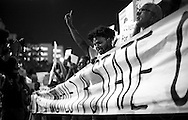"Marching in downtown Miami against President-elect Donald Trump, a group of people leading the march of several hundreds down Biscayne Blvd toward I-95 holds a sign with the message ""ALL OPPRESSION CREATES A STATE OF WAR."""