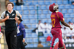 © Licensed to London News Pictures. 01/10/2012. New Zealander Doug Bracewell runs past West Indian Andre Russell after getting his wicket during the T20 Cricket World super 8's match between New Zealand Vs West Indies at the Pallekele International Stadium Cricket Stadium, Pallekele. Photo credit : Asanka Brendon Ratnayake/LNP