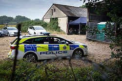 © Licensed to London News Pictures. 11/08/2020. Bisley, UK. Police guard the entrance to Priest Lane Farm near Bisley in Surrey as investigators carry out an historic murder investigation. Surrey Police, supported by the British Army and specialist forensic teams are carrying out a dig in relation to the murder of Tina Baker, 41, in 2002. Tina was initially reported missing after last being seen in Sunbury on 8 July 2002 but the investigation became a murder enquiry in October 2002. In 2005, following an extensive investigation by the Surrey and Sussex Major Crime Team, Tina's husband, Martin Gerald Baker, was arrested and charged with her murder. In 2006, he was sentenced to 14 years behind bars. Tina's body was never recovered. Following the conviction, enquiries continued by Surrey Police in order to find out what happened to Tina Baker's body. Information received has resulted in the decision to carry out forensic investigations in Bisley. Photo credit: Peter Macdiarmid/LNP