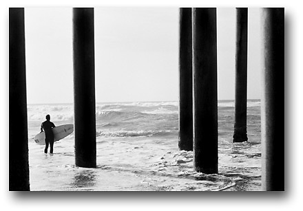 Surfer gets ready to paddle out during a large swell in Huntington Beach, CA