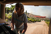 22 JUNE 2005 - CAVE CREEK, AZ:   A homeowner packs her car during the evacuation while a plane drops retardant on the Cave Creek Complex, a large wild fire which burned northeast of Phoenix. The Cave Creek Complex fire was the third largest wildfire in the state of Arizona to date, after the Rodeo-Chediski fire and Wallow Fire. The fire started on June 21, 2005 by a lightning strike during a monsoon storm and burned 243,950 acres (987.2 km2).   PHOTO BY JACK KURTZ