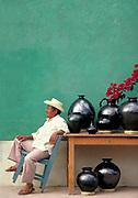 Artist portrait against green wall with black pots, Oaxaca, Mexico