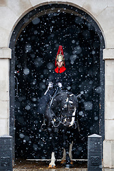 © Licensed to London News Pictures. 10/12/2017. London, UK. Members of the Household Cavalry guard the entrance to Horse Guards Arch as snow falls over Horse Guards Parade in London on Sunday, 10 December 2017. Photo credit: Tolga Akmen/LNP