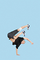 Male break dancer performing handstand over blue background
