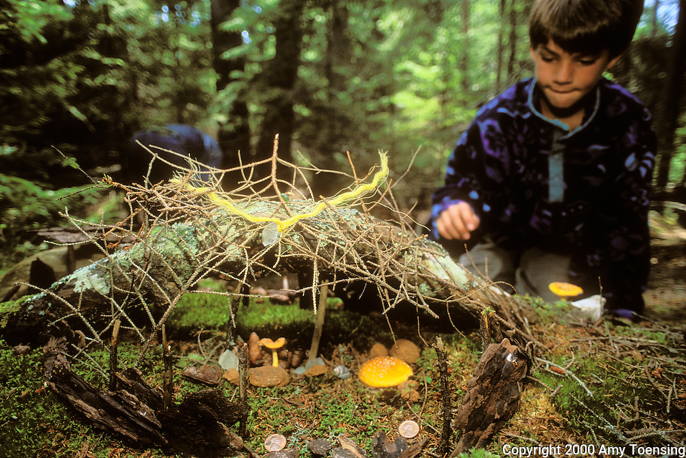 MONHEGAN ISLAND, MAINE - JULY 24: A child builds a fairy house out of natural materials from the Cathedral Woods, July 24, 2000 on Monhegan Island, Maine. Monhegan Island, home to lobstermen and painters and a popular destination for tourists is twelve miles off the coast of Maine. Ringed by high, dark cliffs, its interior a mix of meadows, marsh and spruce groves, Monhegan is one of just 14 true island communities left off the coast of Maine. The island has a 65 permanent, year-round residents and the population grows to around 200 in the summer, with day-trippers adding several hundred more. (Photo by Amy Toensing) _________________________________________<br />