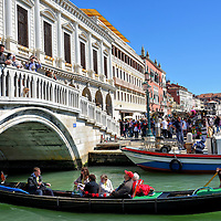 Gondola Under Ponte della Paglia in Venice, Italy<br /> This gondola is floating beneath Ponte della Paglia. This Straw Bridge name dates back to the 14th century when merchants unloaded straw here. The Venetian watercrafts seem simple but each wooden rowboat takes about 500 hours to build by a master squerarolo.  Some unique features include the oarlocks, called fórcolo, that allow the gondolier total steering and power flexibility through narrow canals.  The left side is taller than the right to aid balance, and each piece of ornamentation has historic symbolism.