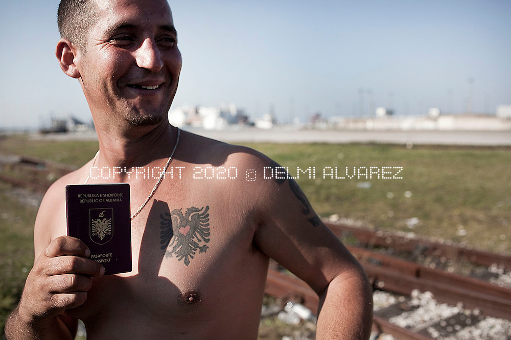 Calais, France, sept 29 2011. Albanian showing his tattoo of Albania flag in his body and passport. He has family in England and waits the opportunity to cross the channel and find his family.In this small city port from where ferries cross the channel to England there is a big community of peoplem (men mostly) waiting the moment to hide in the 5000 lorries that everyday goes with cargo to UK. Hundred of immigants from Sudan, Eritrea, Albania, Irak, Iran and Afghanistan try every night to be one of the luckies to cross. Dogs used by french police find this people under the lorries and the police refused them to Calais.