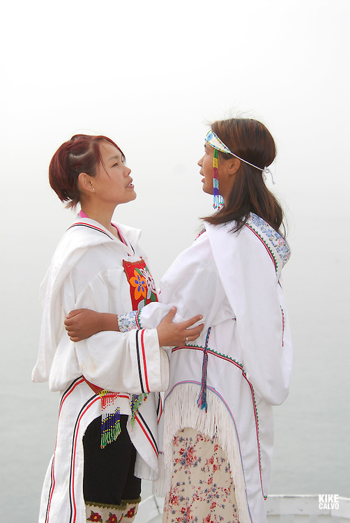 Model released inuit teens throat singing, wearing their traditional clothing. (MR). Pond Inlet, Baffin Island. High Arctic. Canada&amp;#xA;( isolated, remote, tourist, hike, hiking, foggy, weather, rock, rockly. tongue, indigenous, local, folklore, dress, boots,<br />