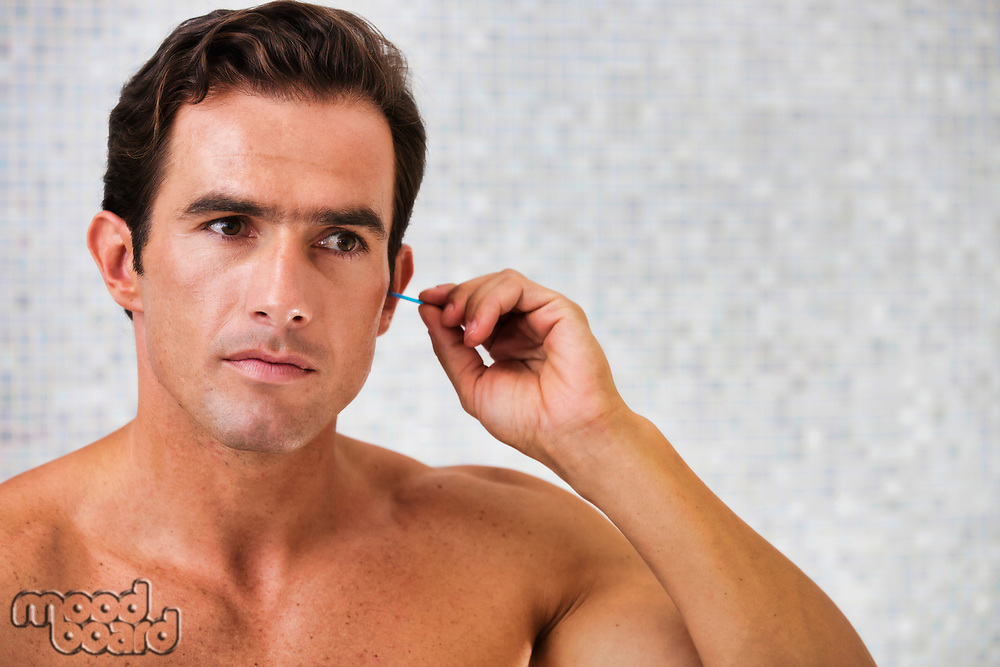 Portrait of young attractive man cleaning his ears with cotton buds in the bathroom