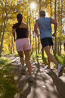 Couple jogging through woodland rear view