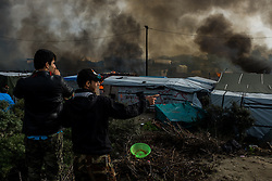 October 26, 2016 - Calais, France - Migrants film in the Calais Jungle the fires, on October 26, 2016. Huge fires destroyed a mayor part of the refugee camp today. (Credit Image: © Markus Heine/NurPhoto via ZUMA Press)