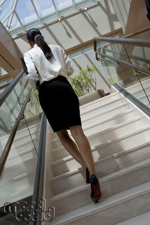 Business woman going upstairs in office building