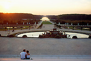 France, Palace of Versailles, couple overlooking Latona Fountain and The Grand Canal at sunset.