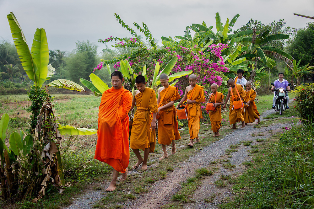 Young novice monks walk for alms in rural Nakhon Nayok, Thailand. PHOTO BY LEE CRAKER
