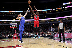 November 12, 2018 - Chicago, IL, USA - Chicago Bulls forward Justin Holiday (7) shoots a three-point-goal over Dallas Mavericks forward Luka Doncic (77) during the first half at the United Center Monday, Nov. 12, 2018 in Chicago. (Credit Image: © Armando L. Sanchez/Chicago Tribune/TNS via ZUMA Wire)
