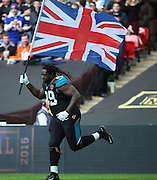 Jacksonville Jaguars Sen Derrick Marks running with the Union Jack onto the field at the start of the game during the Buffalo Bills v Jacksonville Jaguars NFL International Series match at Wembley Stadium, London, England on 25 October 2015. Photo by Matthew Redman.