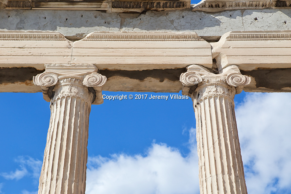 Detail of two of the six long Ionic columns at the entrance of the Erechtheion.<br /> <br /> Named after the demi-god Erechtheus, the mythical Athenian king, the temple was constructed between 421-406 BC, to house the ancient wooden cult statue of Athena.