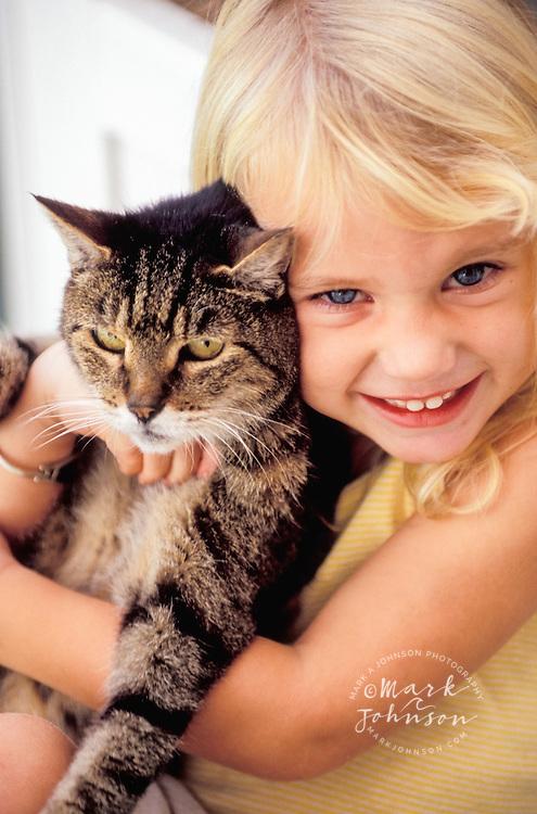 Hawaii, USA --- Girl Embracing Pet Cat