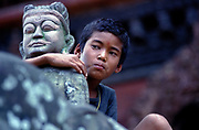 A Nepalese boy holds, unwittingly, onto a temple adornment in Patan's Durbar Square.