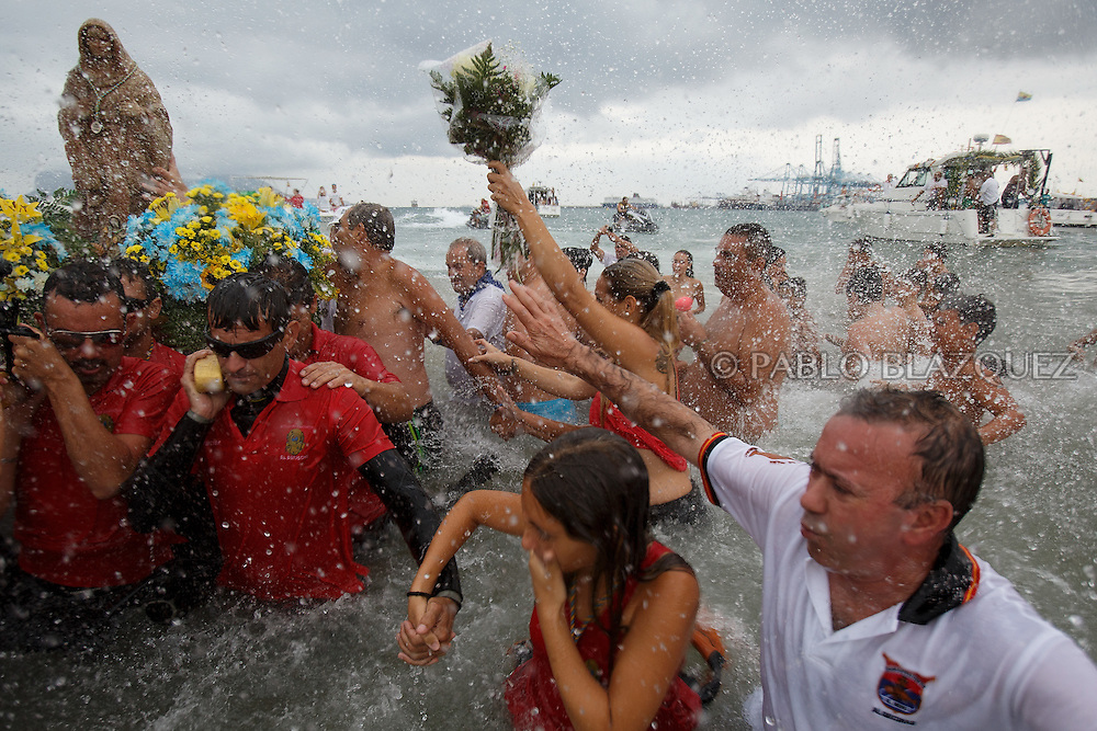 15/08/2016. Divers carry the image of the Virgin of Palm as worshippers splash water as it arrives to the Rinconcillo beach during the yearly Virgin of Palm maritime pilgrimage on August 15, 2016 in Algeciras, Spain. The Our Lady of Palm maritime pilgrimage in Algeciras dates back to 1975 and takes place annually when fishermen rescue the submerged virgin from the deep sea. Worshippers amid thousands of visitors await its arrival at the Rinconcillo beach. The devotion for the Virgin of Palm comes from the seventeenth century when a ship coming from Italy docked at Algeciras port to wait out bad weather. According to legend, once the crew of the ship removed a box with an image of the Virgin from its cargo the weather turned and the sea's tides were calmed. (© Pablo Blazquez)
