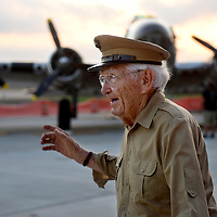 Claude Hone, a Marine Corps World War II fighter pilot, walks past the B-17 Sentimental Journey, a bomber, during the Joe Foss Squadron Fundraiser Hangar Dance at the Maverick Air Center on Thursday evening.  The fundraiser had over a dozen World War II aircraft on the ramp to kick off the Sioux Falls Air Show.