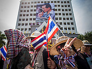 30 NOVEMBER 2013 - BANGKOK, THAILAND:   Anti-government protestors file past a large portrait of Bhumibol Adulyadej, the King of Thailand, that hangs on the DSI, or Police Department of Special Investigation, an elite police investigative unit, in Bangkok. Political faultlines in Bangkok, the Thai capital, hardened Saturday. Antigovernment factions repeated promises to strike at the heart of Bangkok Sunday and bring down the government while thousands of Red Shirts, who support the government, have come to Bangkok from their base in rural Thailand to defend the government. Prime Minister Yingluck Shinawatra has appealed for calm, but her opponents have rejected all requests for negotiations saying the only acceptable outcome is the eradication of the government.       PHOTO BY JACK KURTZ