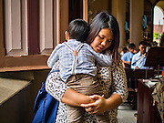 27 MARCH 2016 - BANGKOK, THAILAND: A woman hold her son while she prays during Easter services at Santa Cruz Church in Bangkok. Santa Cruz was one of the first Catholic churches established in Bangkok. It was built in the late 1700s by Portuguese soldiers allied with King Taksin the Great in his battles against the Burmese who invaded Thailand (then Siam). There are about 300,000 Catholics in Thailand, in 10 dioceses with 436 parishes. Easter marks the resurrection of Jesus after his crucifixion and is celebrated in Christian communities around the world.      PHOTO BY JACK KURTZ