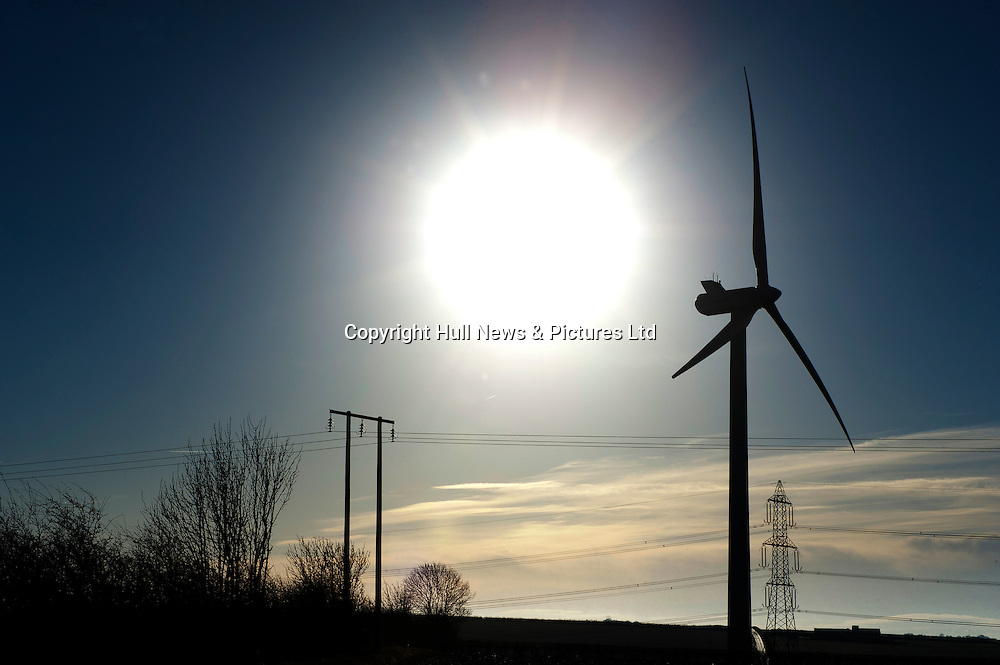 The winter sun behind wind turbines, a pylon and electricity poles at Sancton Hill, East Yorkshire, situated within the Yorkshire Wolds.