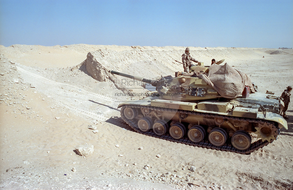 Egyptian soldiers positions a M60 battle tank along the sand berm border wall on the frontline separating Kuwait from Saudi Arabia February 8, 1991 in Ar Ruqi, Saudi Arabia.
