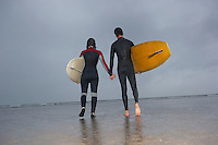 Couple of surfers carrying surfboards walking on beach back view