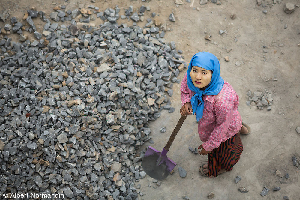 Woman labourer, shovelling rocks, looks up, Pathein road to Yangon