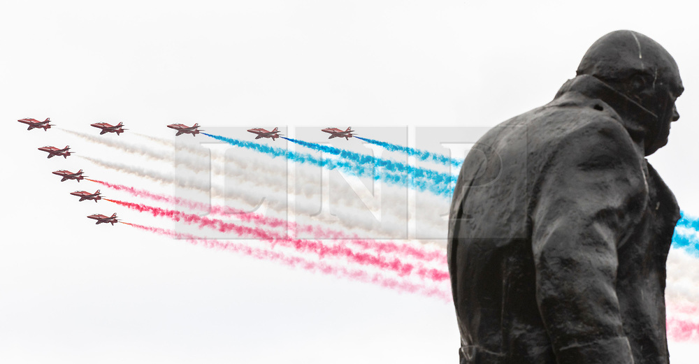 © Licensed to London News Pictures. 10/07/2018. London, UK. The RAF Red Arrows fly past the Winston Churchill statue in Parliament Square, trailing red white and blue smoke, to conclude the RAF100 flypast which celebrates the centenary of the Royal Air Force. Photo credit: Rob Pinney/LNP