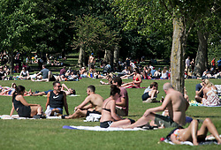 © Licensed to London News Pictures. 25/05/2020. London, UK. Members of the public sit out on Queens Park in west London, on a warm summers day during lockdown. Government has announced a series of measures to slowly ease lockdown, which was introduced to fight the spread of the COVID-19 strain of coronavirus. Photo credit: Ben Cawthra/LNP