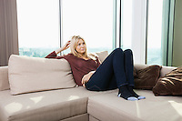 Thoughtful young woman sitting on sofa against window at home