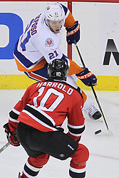 Apr 3; Newark, NJ, USA; New York Islanders right wing Kyle Okposo (21) skates with the puck while being defended by New Jersey Devils defenseman Peter Harrold (10) during the third period at the Prudential Center.  The Devils defeated the Islanders 3-1.