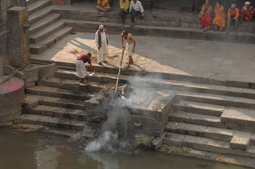 Attendants sweep the ashes of a cremated police officer into the Bagmati river, at Pashupatinath Temple, in Kathmandu, Nepal.