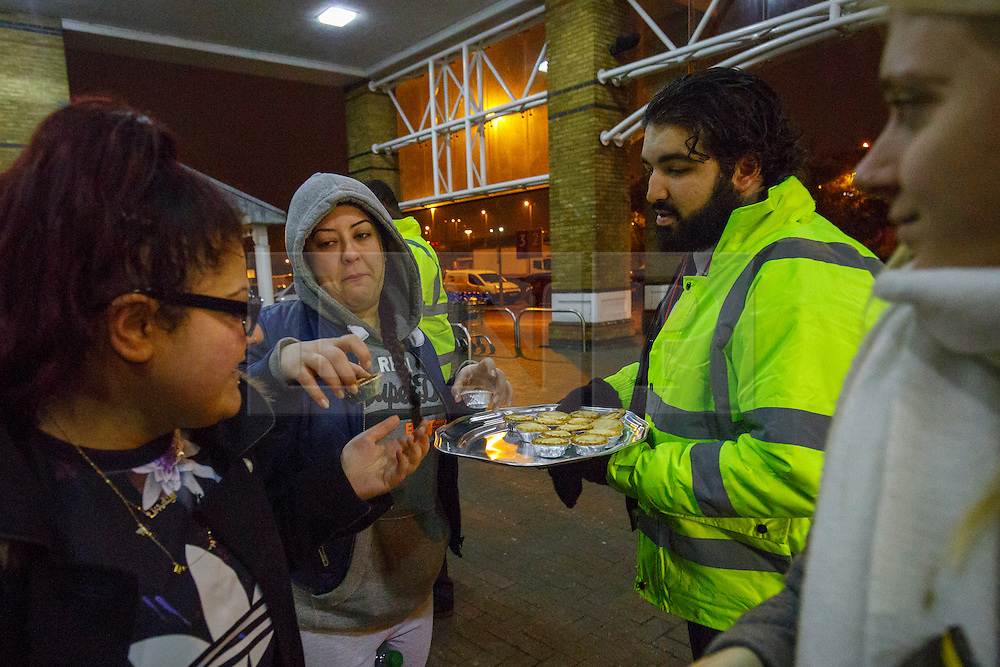 © Licensed to London News Pictures. 26/11/2015. London, UK. Tesco stuff handing out mince pies to Black Friday shoppers queueing outside a Tesco Extra store in Edmonton, north London on Friday, 27 November 2015. Photo credit: Tolga Akmen/LNP