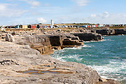Old white lighthouse now a bird observatory and beach huts on the coast at Portland Bill, Isle of Portland, Dorset, England