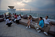 State Tower. Customers of Distil Bar enjoy a splendid sunset panoramic of Bangkok.
