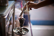 07 JULY 2011 - BANGKOK, THAILAND: An attendant puts hot coals into a customer's hookah while he smokes shisha at the Nefertiti Restaurant, an Egyptian restaurant in the Soi Arab neighborhood of Bangkok. Soi Arab started as an alleyway in Bangkok (Soi is the Thai word for alley or small street). What started as an alley has now grown into a neighborhood that encompasses several blocks of restaurants, hotels and money exchanges that cater to Middle Eastern visitors to Thailand. The official name of the street is Sukhumvit Soi 3/1, located in North Nana between Sukhumvit Soi 3 and Sukhumvit Soi 5, not far from the Nana Plaza night-life area and the Grace Hotel popular among Arabs.    PHOTO BY JACK KURTZ