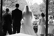 Bride and groom during ceremony from behind look at guests in Black and White