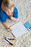 Portrait of blond hair boy lying on rug doing homework