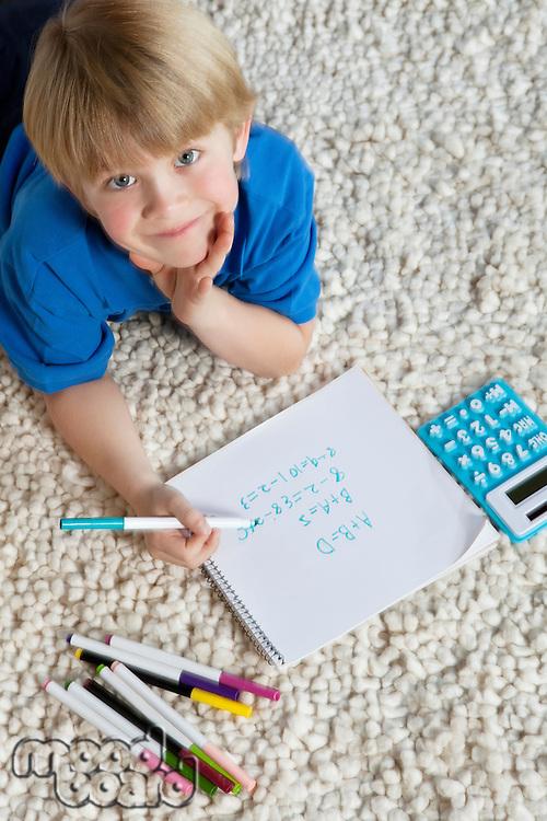 Portrait of blond hair boy lying on rug doing homework