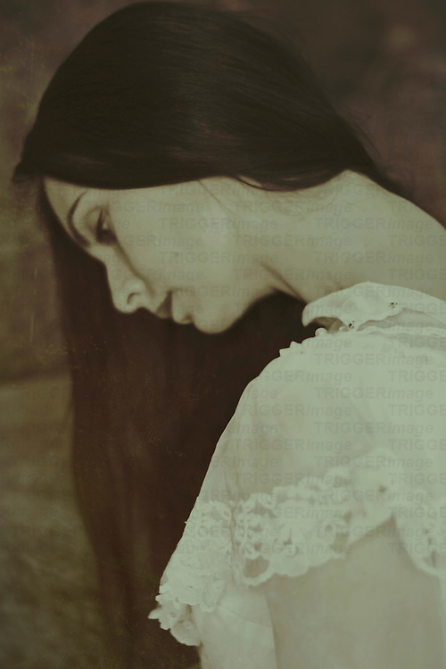 a monochrome portrait of a woman's profile in sepia tone, head shot, with dark long hair and white blouse